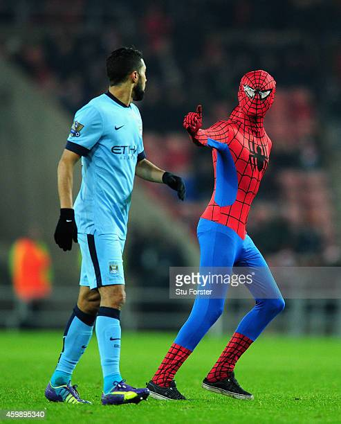 A spectator dressed as Spiderman approaches Manchester City player Gael Clichy during the Barclays Premier League match between Sunderland and...