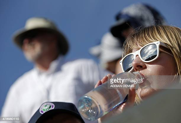 A spectator drinks from a bottle as she watches a match in the sun on day one of the 2015 Wimbledon Championships at The All England Tennis Club in...