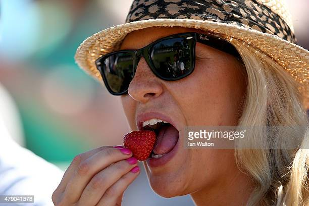 Spectator eats a strawberry during day two of the Wimbledon Lawn Tennis Championships at the All England Lawn Tennis and Croquet Club on June 30 2015...