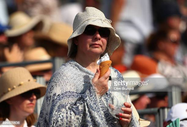 A spectator eats an ice cream as she watches on during the mens singles second round match between Grigor Dimitrov of Bulgaria and Julien Benneteau...