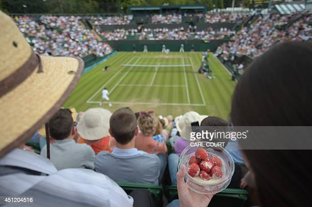 A spectator eats strawberries and cream as she watches Spain's David Ferrer play against Russia's Andrey Kuznetsov during their men's singles second...