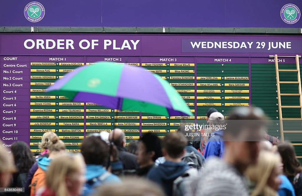 A spectator holds an umbrella as they walk by the order of play board on display on the rain delayed the third day of the 2016 Wimbledon Championships at The All England Lawn Tennis Club in Wimbledon, southwest London, on June 29, 2016. / AFP / JUSTIN