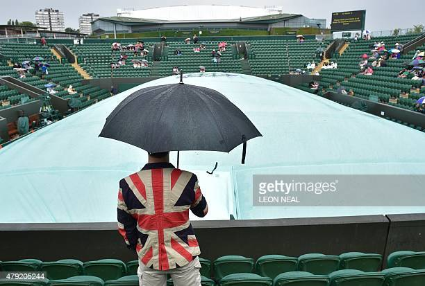 A spectator in a Union Flag jacket shelters from the rain beneath an umbrella as he waits for play to commence on day four of the 2015 Wimbledon...