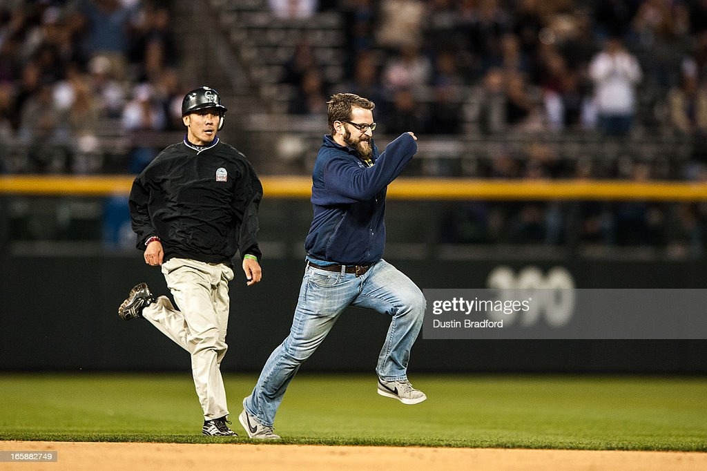 A spectator is chased across the infielder by a member of Coors Field on-field security during the eighth inning of a game between the Colorado Rockies and the San Diego Padres at Coors Field on April 6, 2013 in Denver, Colorado. The Rockies Beat the Padres 6-3.
