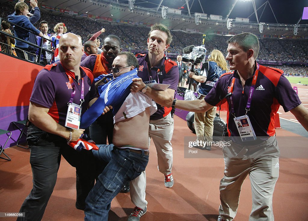 A spectator is detained by security after a beer bottle was thrown on to the track during the start of the men's 100 metres final, on Day 9 of the London 2012 Olympic Games at the Olympic Stadium on August 5, 2012 in London, England.