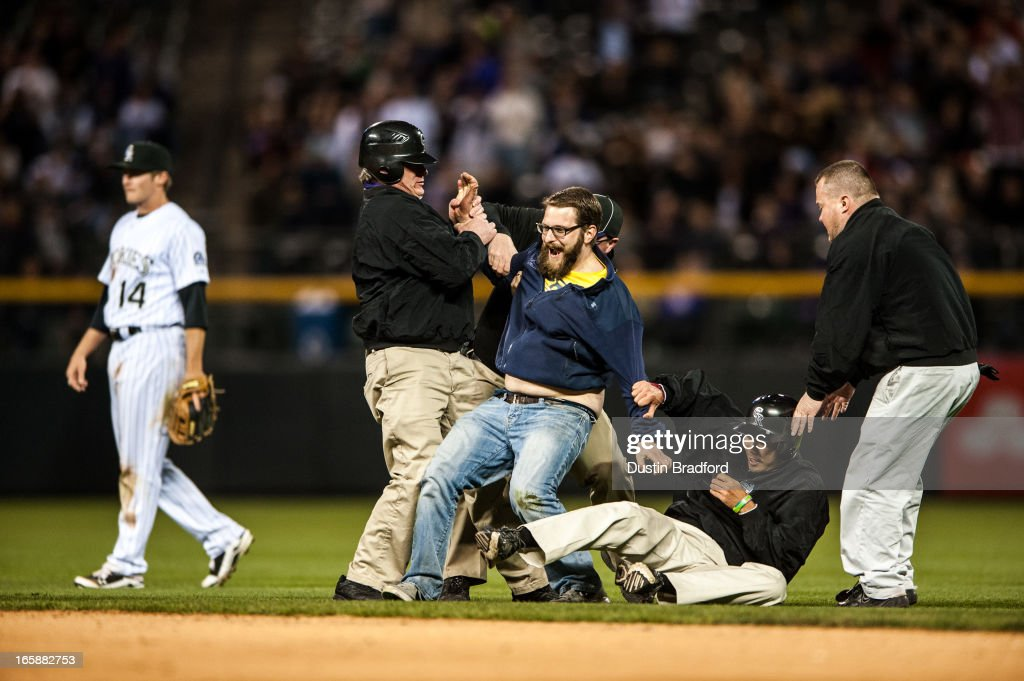 A spectator is restrained in the infield by members of Coors Field on-field security during the eighth inning of a game between the Colorado Rockies and the San Diego Padres at Coors Field on April 6, 2013 in Denver, Colorado. The Rockies Beat the Padres 6-3.