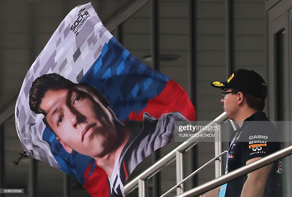A spectator looks at a flag with a picture of Red Bull Racing's Russian driver Daniil Kvyat during the qualifying session of the Formula One Russian Grand Prix at the Sochi Autodrom circuit on April 30, 2016. / AFP / POOL / YURI