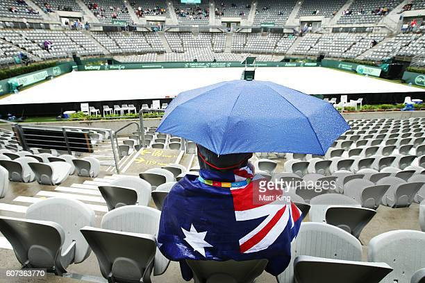 A spectator looks on as rain delays the start of play during the Davis Cup World Group playoff between Australia and Slovakia at Sydney Olympic Park...
