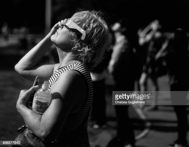 A spectator looks skyward during the partial solar eclipse at peak time on August 21 2017 in Los Angeles California