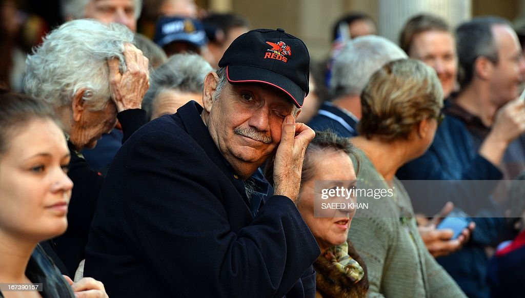 A spectator reacts while watching the Anzac Day march in Sydney on April 25, 2013. Tens of thousands of Australians and New Zealanders turned out on April 25 to honour their war dead, with moving tributes to fallen mates and calls not to forget those injured in conflict. AFP PHOTO / Saeed Khan