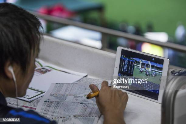 A spectator reads a newspaper as an electronic tablet shows a video of horses crossing the finish line during a race at the Hong Kong Jockey Club's...