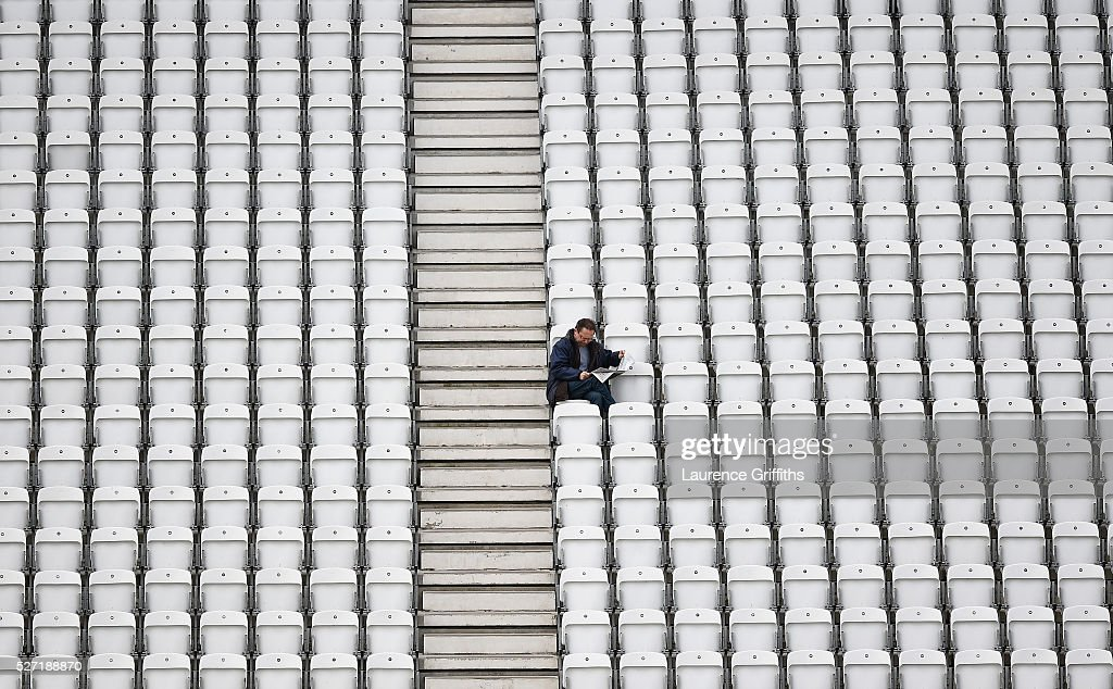 A spectator reads the newspaper as he waits for the rain to stop during the Specsavers County Championship Division One match between Nottinghamshire and Yorkshire at Trent Bridge on May 2, 2016 in Nottingham, England.