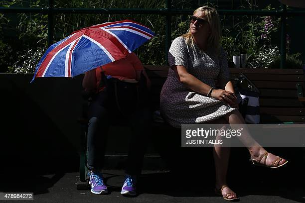A spectator shades themselves under a Union Flag umbrella on day one of the 2015 Wimbledon Championships at The All England Tennis Club in Wimbledon...