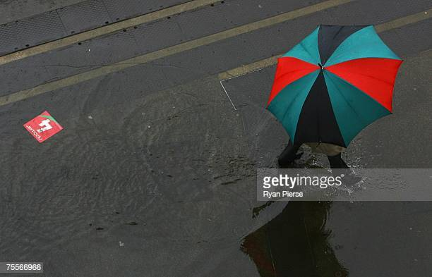 A spectator shelters from the heavy rain during day two of the First Test match between England and India at Lord's on July 20 2007 in London England