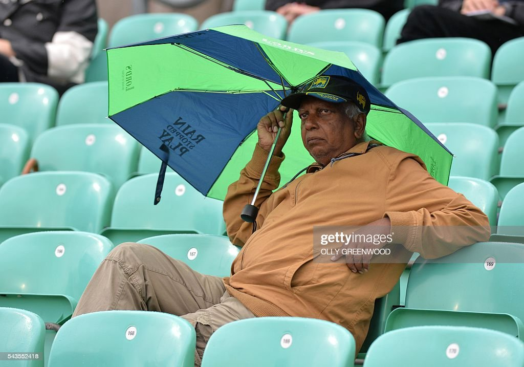 A spectator shelters from the rain under an umbrella during a rain delay in the fourth One Day International (ODI) cricket match between England and Sri Lanka at The Oval cricket ground in London on June 29, 2016. England captain Eoin Morgan elected to field after winning the toss in the fourth one-day international against Sri Lanka at The Oval on Wednesday. With light rain around and dark grey skies, Morgan clearly felt his bowlers could utilise the favourable bowling conditions with further down pours forecast during the afternoon and evening. ECB