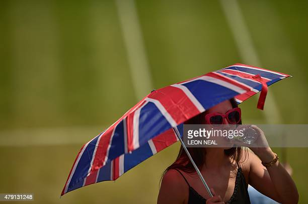A spectator shelters from the Sun beneath a Union Flagthemed umbrella as she drinks water between matches on day three of the 2015 Wimbledon...