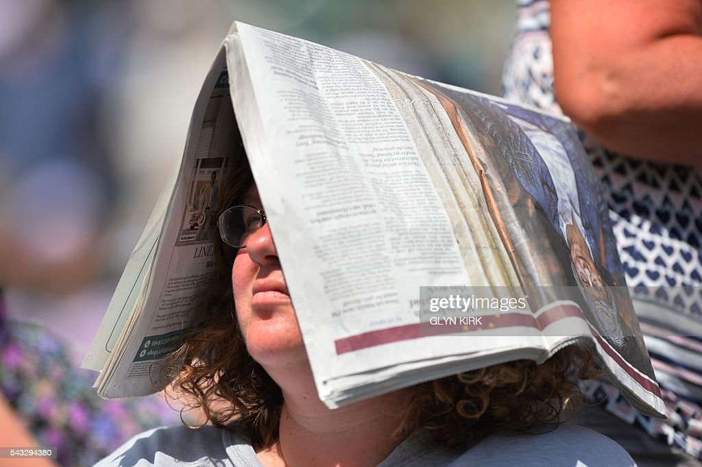 A spectator shields her head from the sun with a newspaper on No 1 Court at The All England Lawn Tennis Club in Wimbledon, southwest London, on June 27, 2016 on the first day of the 2016 Wimbledon Championships. / AFP / GLYN
