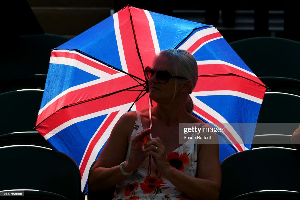 A spectator shields themselves from the sun on day four of the Wimbledon Lawn Tennis Championships at the All England Lawn Tennis and Croquet Club on July 6, 2017 in London, England.