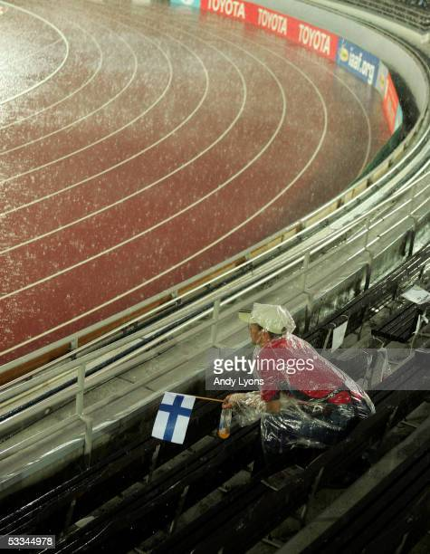 A spectator sits in the rain during a rain delay at the 10th IAAF World Athletics Championships on August 9 2005 in Helsinki Finland