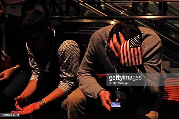 A spectator sits on a bench on his Apple iPhone while waiting for Republican presidential candidate Mitt Romney to concede his presidency during Mitt...
