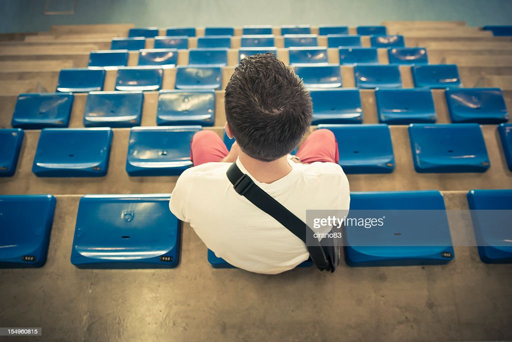 Spectator Sitting On Stadium Bleachers, Watching A Match