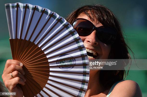 A spectator smiles as she uses a fan to cool off on day two of the 2015 Wimbledon Championships at The All England Tennis Club in Wimbledon southwest...