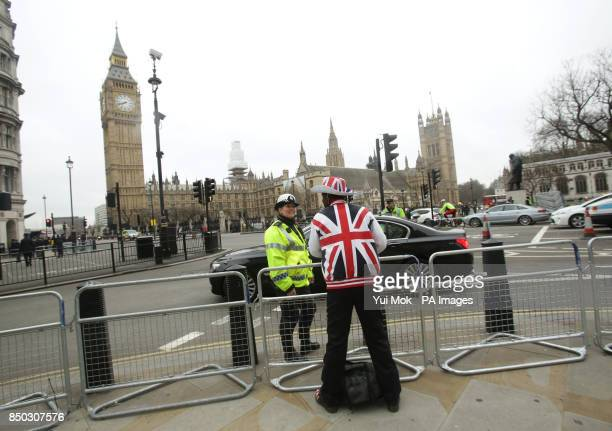 A spectator sporting a Union Flag hat and coat chats to a police officer at Parliament Square prior to the funeral service of Baroness Thatcher at St...