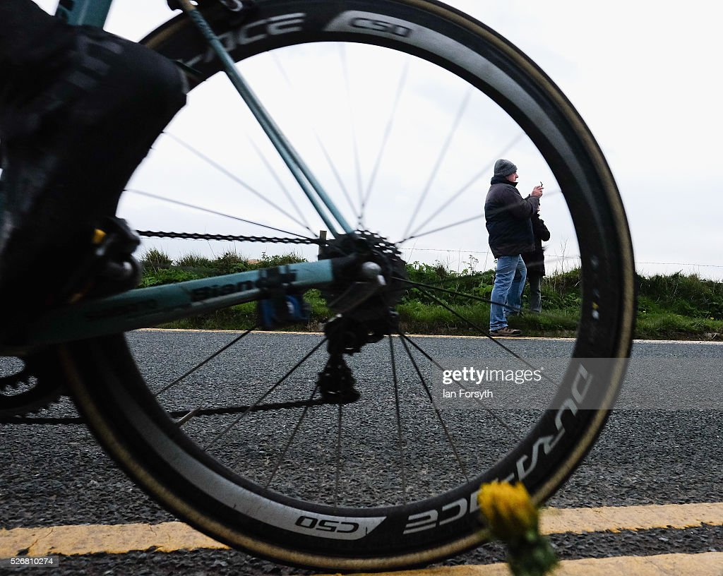 A spectator stands on the side of the road as a rider competes in stage three of the Tour de Yorkshire cycle race rides by on May 1, 2016 in Whitby, England. Returning for a second year the hugely popular race has grown to be one of the most spectacular events in the British sporting calendar. Up to a million people have lined the route along the three stages of the race which ends today with the 198km Middlesbrough to Scarborough leg.