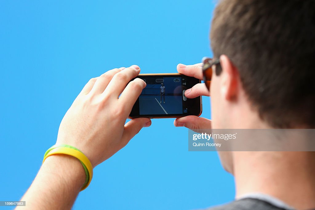 A spectator takes a photo of Laura Robson of Great Britain on his smartphone during day five of the 2013 Australian Open at Melbourne Park on January 18, 2013 in Melbourne, Australia.