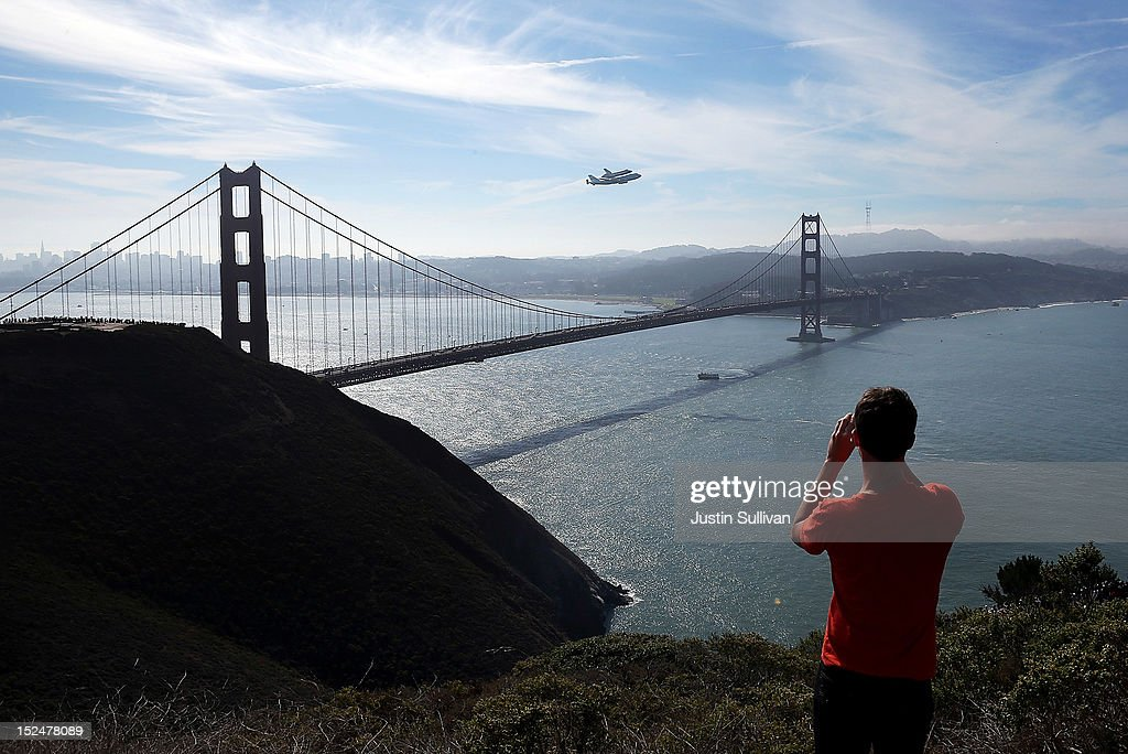 A spectator takes a photo of the Space Shuttle Endavour as it flies on top of a modified 747 jumbo jet over the Golden Gate Bridge while traveling to Los Angeles on September 21, 2012 in Sausalito, California. The Space Shuttle Endeavour did a 4-1/2 hour tour over California landmarks before heading to Los Angeles International Airport where it will be prepared to be moved to its new permanent home at the California Science Center in downtown Los Angeles. The shuttle will be on public display starting October 30.