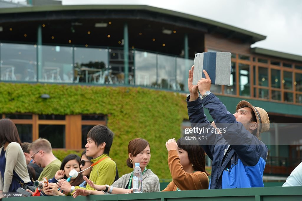 A spectator takes a photographer with a tablet at The All England Lawn Tennis Club in Wimbledon, southwest London, on June 27, 2016 on the first day of the 2016 Wimbledon Championships. / AFP / GLYN
