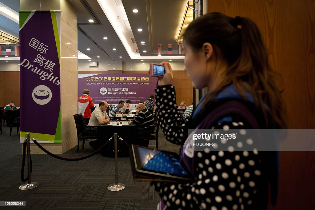 A spectator takes photos of a draughts competition at the Beijing 2012 World Mind Games Tournament in Beijing on December 19, 2012. Some of the world's top chess players went eye-to-eye in the year's highest-level 'blindfold' chess tournament -- seen by some as the toughest challenge in the game. Unable to physically see their own or their opponent's past moves, the players summoned headache-inducing levels of concentration to fight for gold in a silent conference room, lined up in front of laptop screens showing a blank board. AFP PHOTO / Ed Jones