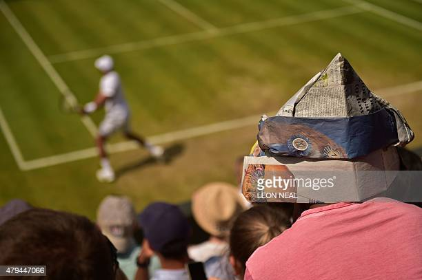A spectator uses a newspaper to shelter from the sun as he watches a match on day six of the 2015 Wimbledon Championships at The All England Tennis...