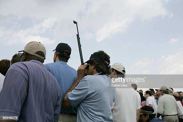 Spectator uses a periscope to see over the crowd during the third round of the Ford Championship at Doral held on the Blue Course at Doral Golf...