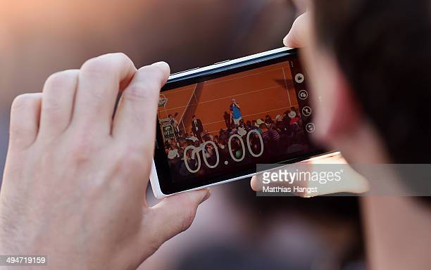 A spectator uses a smartphone to record John Isner of the United States returns as he celebrates victory during his men's singles match against Tommy...