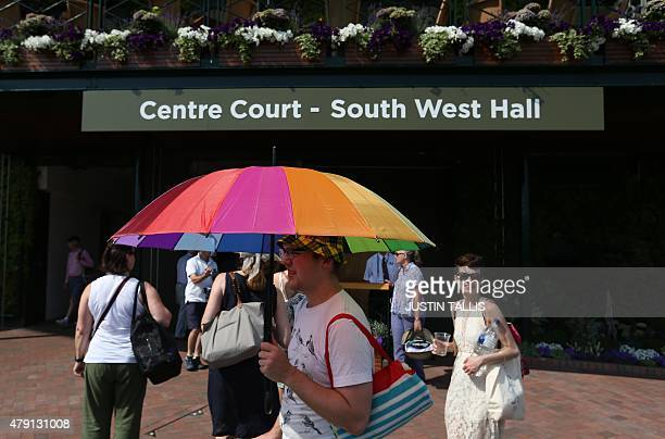 A spectator uses an umbrella to shield him from the sun on day three of the 2015 Wimbledon Championships at The All England Tennis Club in Wimbledon...
