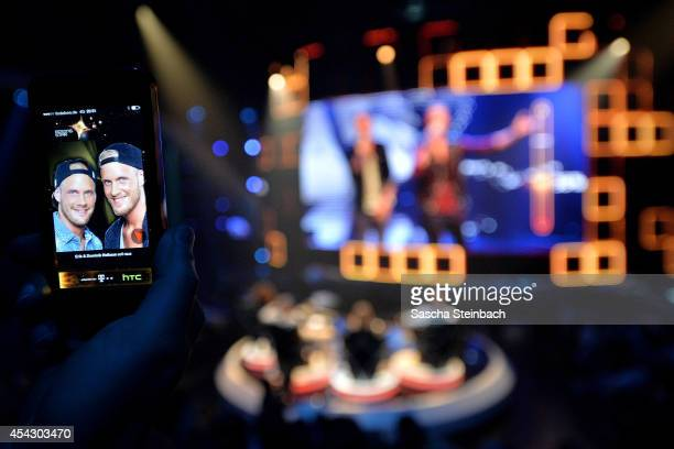 A spectator votes via smartphone app for Erik and Dominik Heikaus during the first live show of 'Rising Star' at Coloneum on August 28 2014 in...