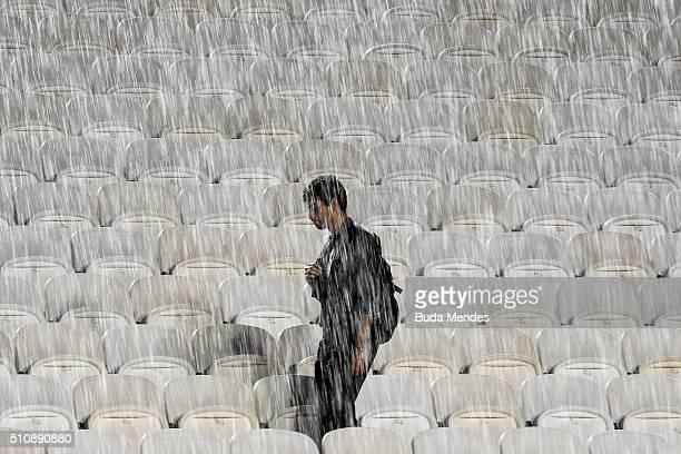 A spectator waits in the stands as rain suspends the match between David Ferrer of Spain and Albert RamosVinolas of Spain during the Rio Open at...