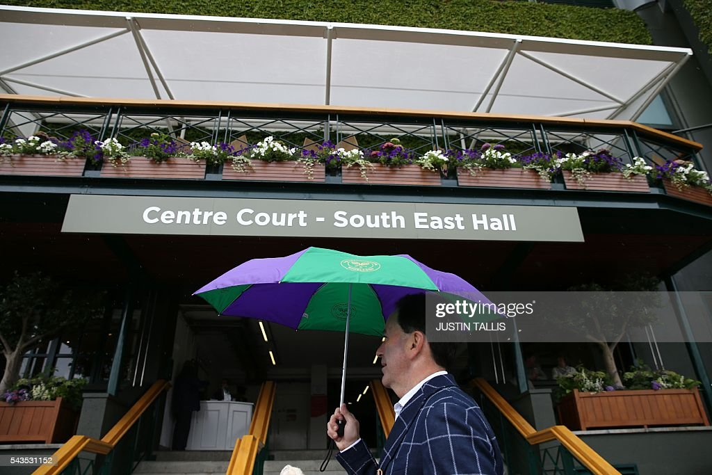 A spectator walks with an umbrella past Centre Court on the rain delayed third day of the 2016 Wimbledon Championships at The All England Lawn Tennis Club in Wimbledon, southwest London, on June 29, 2016. / AFP / JUSTIN