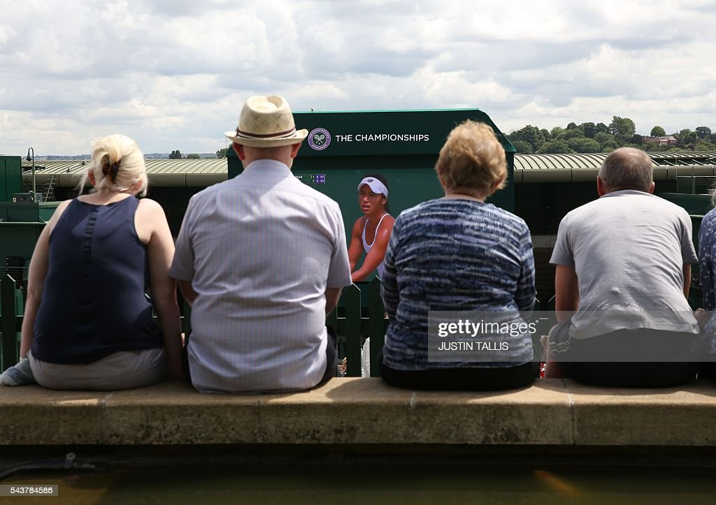 Spectator watch the big screen from Murray mount on the fourth day of the 2016 Wimbledon Championships at The All England Lawn Tennis Club in Wimbledon, southwest London, on June 30, 2016. / AFP / JUSTIN