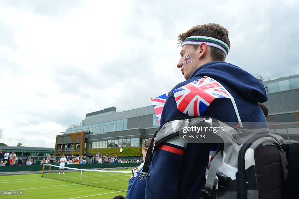 A spectator watches as Serbia's Novak Djokovic (unseen) practices on court 15 ahead of his men's singles first round match against Britain's James Ward on the first day of the 2016 Wimbledon Championships at The All England Lawn Tennis Club in Wimbledon, southwest London, on June 27, 2016. / AFP / GLYN