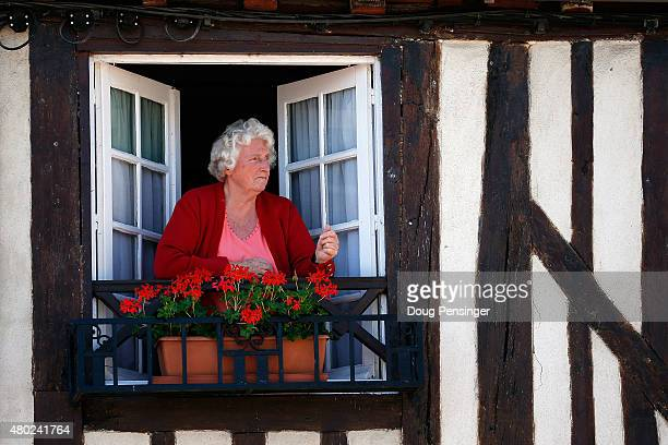 A spectator watches from her window as riders prepare for the start of stage seven of the 2015 Tour de France from Livarot to Fougeres on July 10...