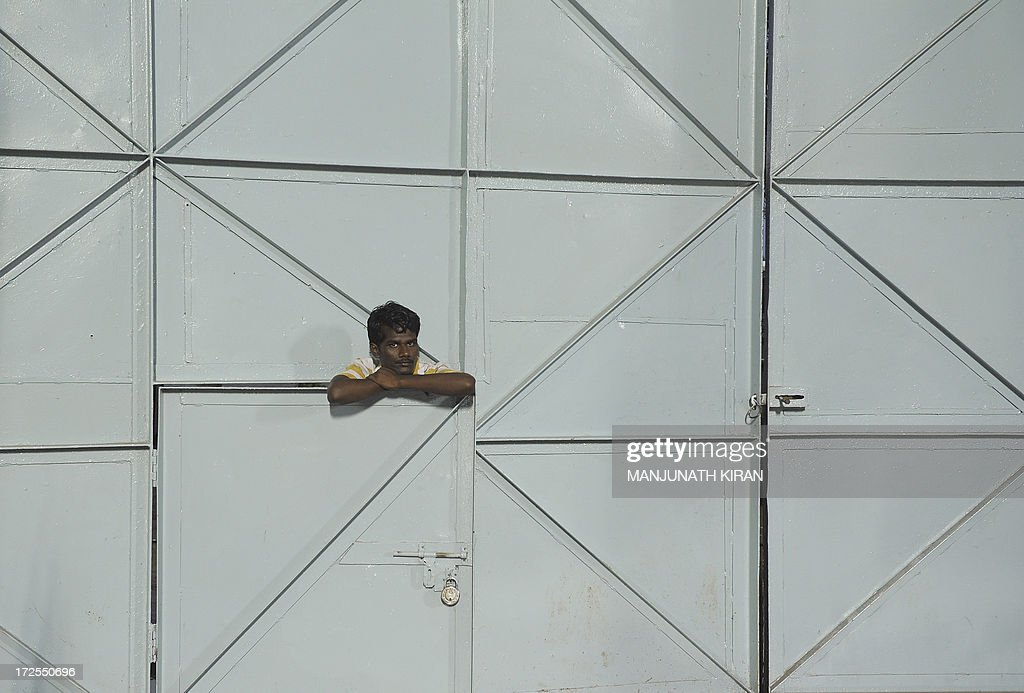 A spectator watches the ongoing games while leaning on a metal door during the first day of the five-day Asian Athletics Championship 2013 at the Chatrapati Shivaji Stadium in Pune on July 3, 2013. AFP PHOTO/Manjunath KIRAN