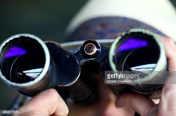 A spectator watches the races through his binoculars at Ascot racecourse on July 11 2015 in Ascot England