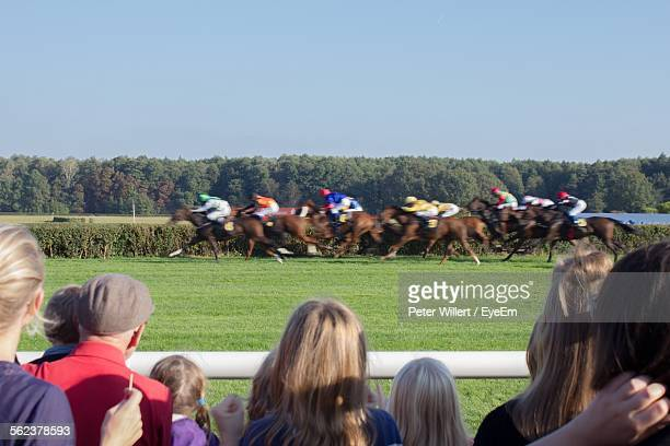 Spectator Watching Horse Race On Grassy Field Against Sky