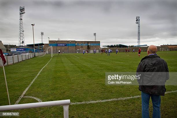 A spectator watching West Lancashire Football League Furness Rovers playing on their Strawberry fields pitch adjacent to Barrow AFC's Furness...