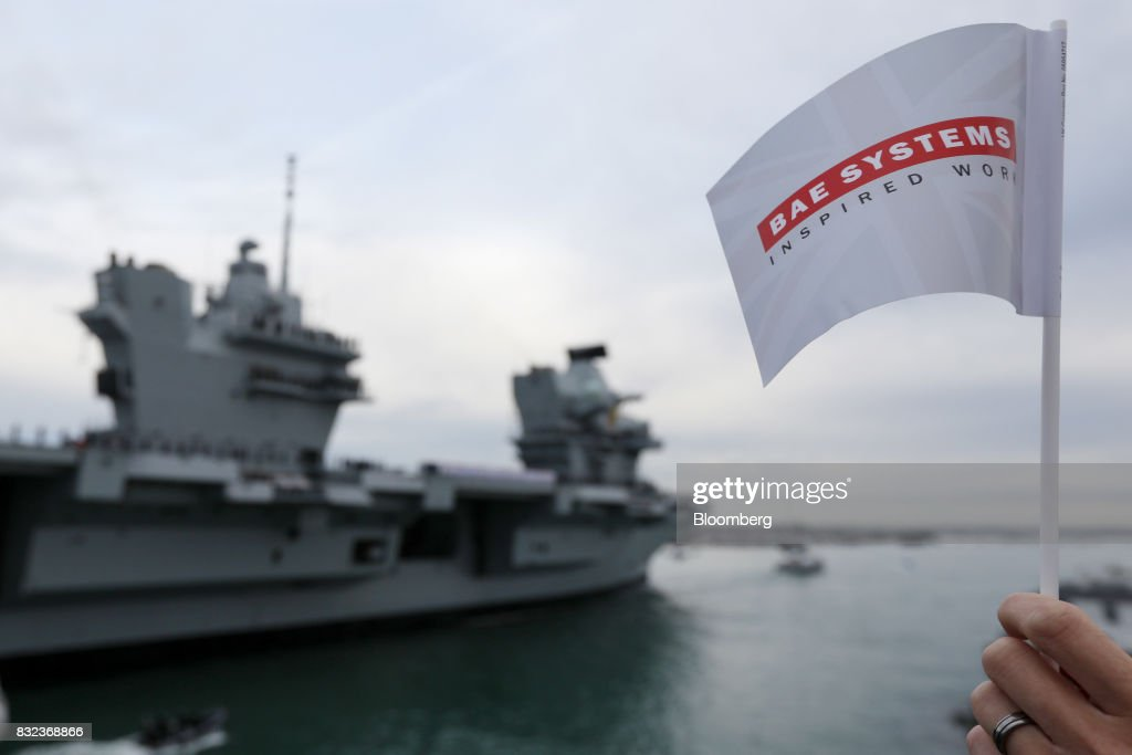 A spectator waves a flag with BAE Systems Plc logo as the U.K.'s Royal Navy new aircraft carrier, HMS Queen Elizabeth arrives at its home port in Portsmouth, U.K., on Wednesday, Aug. 16, 2017. The largely French-designed ship will carry 40 aircraft and about 700 crew members was built by a joint venture between BAE Systems Plc, Babcock International Group Plc and Thales SA. Photographer: Luke MacGregor/Bloomberg via Getty Images