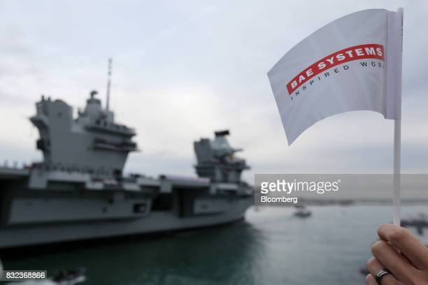 A spectator waves a flag with BAE Systems Plc logo as the UK's Royal Navy new aircraft carrier HMS Queen Elizabeth arrives at its home port in...