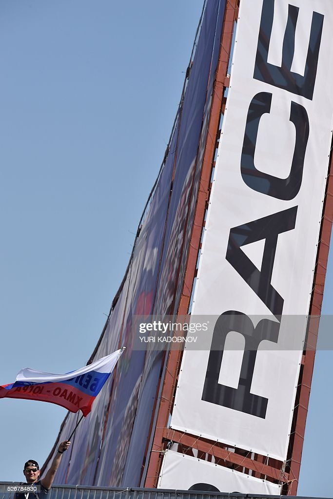 A spectator waves a Russian flag prior to the start of the Formula One Russian Grand Prix at the Sochi Autodrom circuit on May 1, 2016. / AFP / YURI