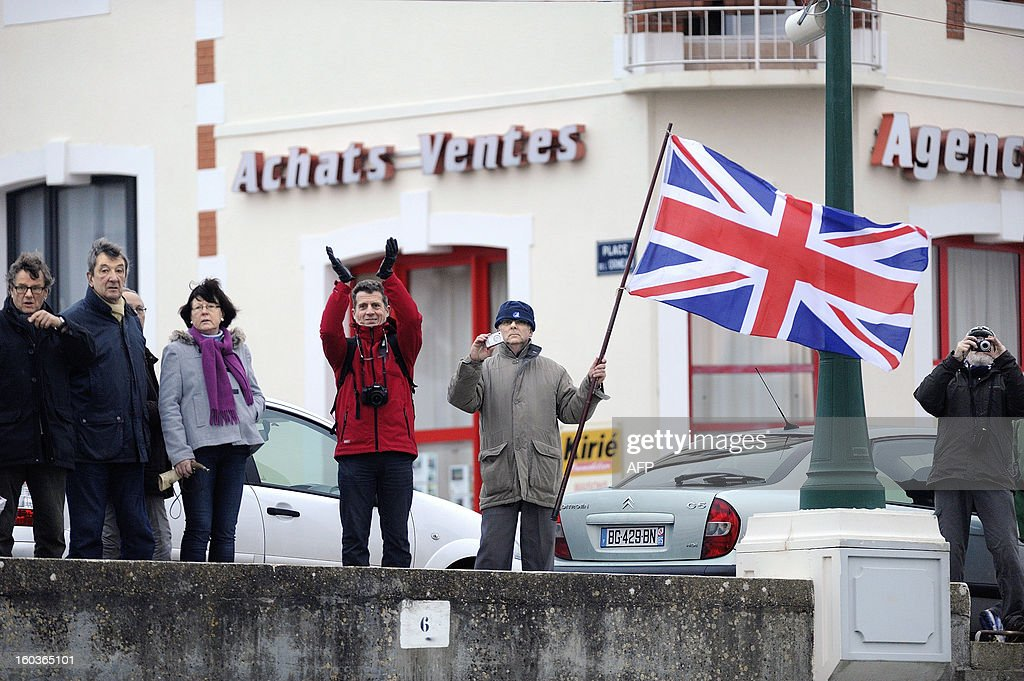 A spectator waves a union jack during the arrival of British skipper Alex Thomson on his monohull 'Hugo Boss' who placed third in the 7th edition of the Vendee Globe solo round-the-world race on January 30, 2013 in Les Sables d'Olonne, western France. AFP PHOTO JEAN-SEBASTIEN EVRARD